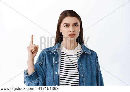 Confused Girl Frowns, Points Up At Something Strange Of , Looks At Camera Doubtful, Shows Top Advert