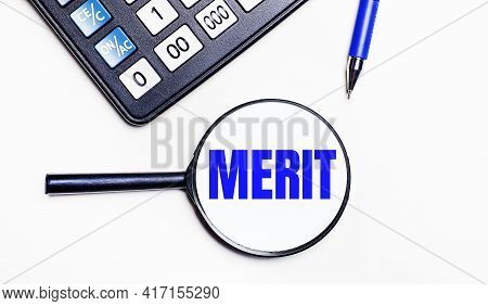 On A Light Background, A Black Calculator, A Blue Pen And A Magnifying Glass With Text Inside The Me