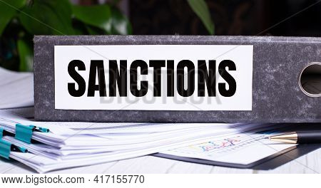 The Word Sanctions Is Written On A Gray File Folder Next To Documents. Business Concept