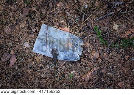 Discarded Plastic Trash In The Forest. In The Forest, On Last Year's Leaves, Lies A Plastic Bottle C