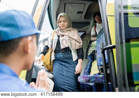 Female Tourist With Rucksack Walking Out From Travel Bus