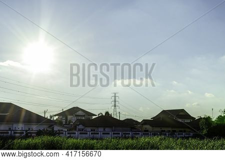 High Voltage Electricity Pylon Over The Roof House, Landscape View Of Electricity Trassmission Line