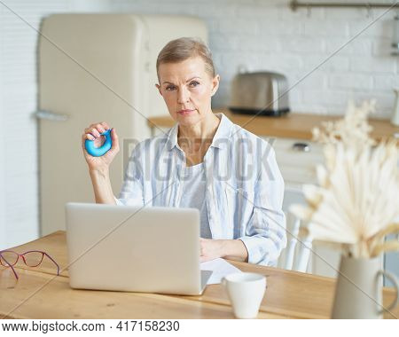 Focused Mature Woman Exercising With Rubber Round Grip Ring For Palms While Working Or Studying On L