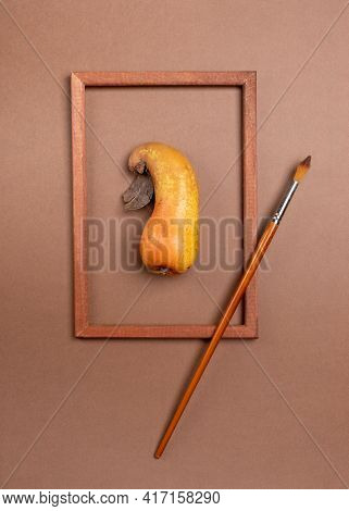 Wooden Frame With Ugly Ripe Pear Inside It And Brush On Brown Background.