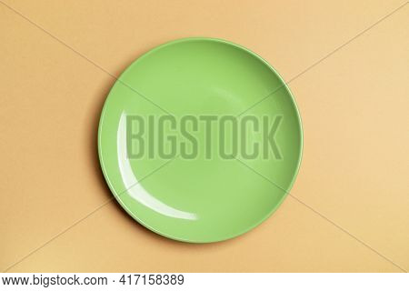 One Green Empty Plate In Center Of Beige Background With Copy Space. Mock Up.