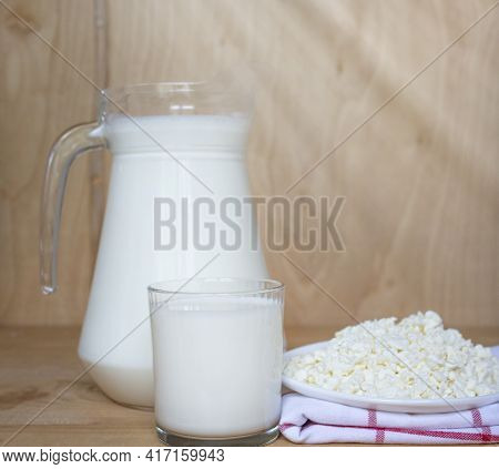 Tasty Fresh Milk On A Wooden Background. Carafe With Milk And A Glass Of Milk, Cottage Cheese.