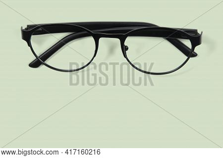Closed Black Eyeglass On Green Background On Top View