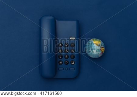 Landline Phone With Globe On Classic Blue Background. Color 2020. Top View