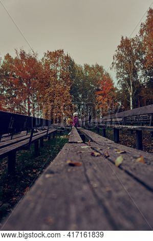 The Girl Is A Child In A Crimson Cloak In The Far Term, With A Bouquet Of Yellow Leaves, Sitting On