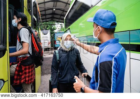A Bus Crew In Uniform And A Hat Using A Thermo Gun Inspects The Passenger Of A Woman In A Veil And M
