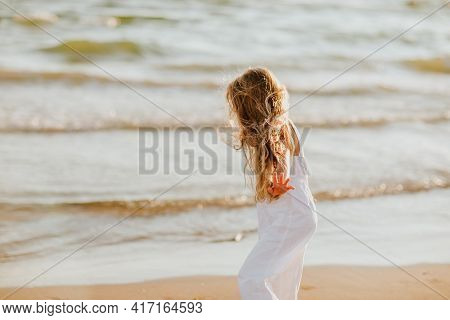 Young Pretty Long Haired Girl In White Summer Overalls Walking On A Sea Coast. Copy Space.