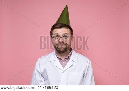 Cute, Contented Doctor In A White Coat And Birthday Hat, Looks In Surprise, He Just Has A Pleasant S