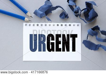 Urgent, Text On White Notepad Paper. Near Torn Blue Paper