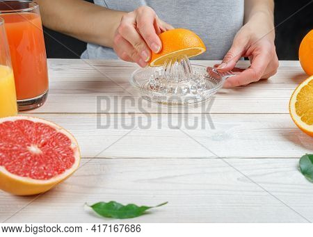 Young Woman Squeezes Orange Juice Using A Manual Glass Juicer.