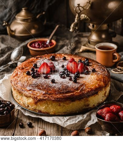 Homemade Cheesecake Or Cottage Cheese Casserole With Berries And Icing Sugar On Rustic Wooden Table