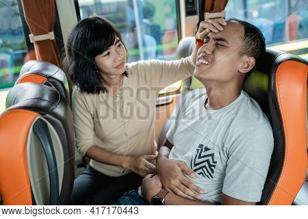 A Man Is Sick And A Woman Holds Her Forehead While Sitting On A Bus Bench