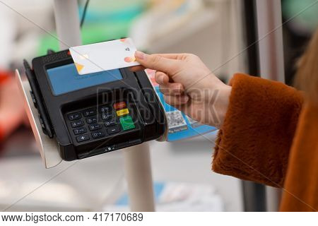 Woman Hand With Credit Bank Card Pays For Purchases At The Checkout Counter In The Store. Contactles