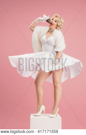 Portrait Of Young Woman In White Dress On Coral Pink Background. Female Model As A Legendary Actress