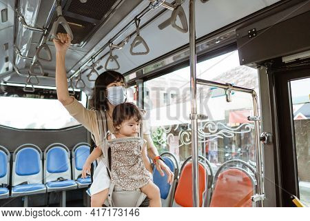 A Mother Wears A Mask And Carries Her Child While Standing On The Bus