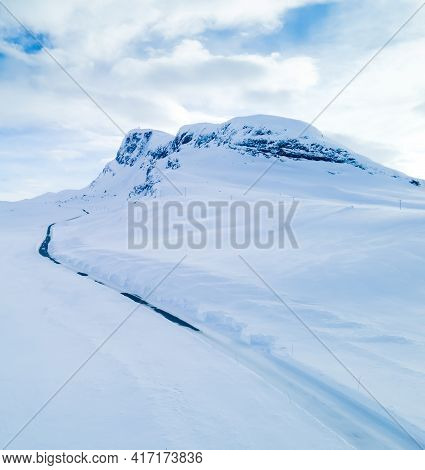 Lonely Road Winding Through A Snow Covered Mountain Landscape On A Cold Winters Day.