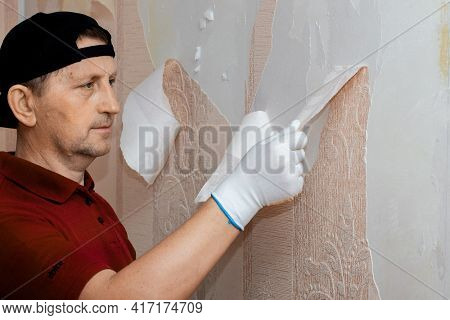 Ukraine, Khmelnytsky Region, April 2021. Man, Repairman Removes Old Wallpaper From The Wall, Replaci