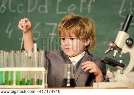 Kid Study Chemistry School Lesson. School Education. Boy Use Microscope And Test Tubes In School Cla