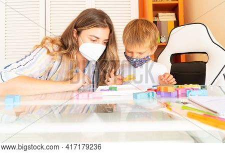 Back To School, Calss Rom With A Teacher And Student Collecting Puzzles Together Wearing Protective