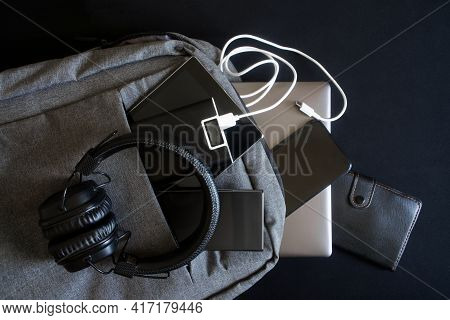 A Lot Of Modern Gadgets: A Laptop, Tablet, Smartphones And A Leather Wallet Are In A Gray Backpack A