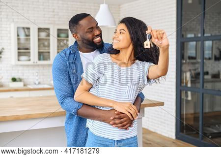The Young African American Happy Married Couple, Man Hugs Beautiful Wife Who Holds The Keys To The A