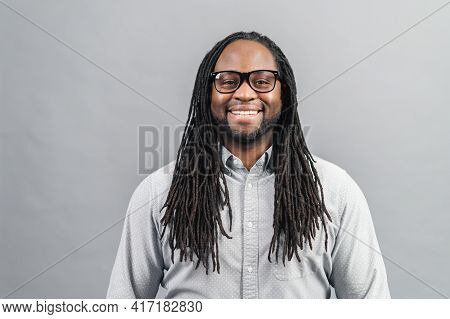 Smiling Young Handsome African American Guy With Dreadlocks In Smart Casual Shirt And Eyeglasses Sta