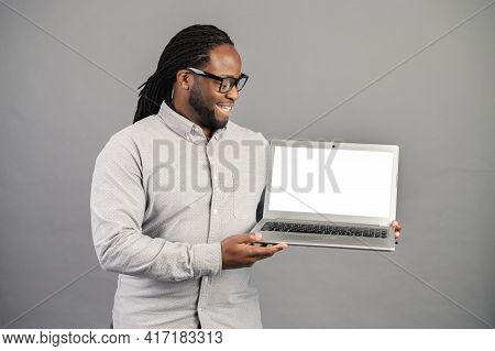 Mixed-race Black Man With Dreadlocks Standing Isolated Over Grey Background, Presenting New Applicat