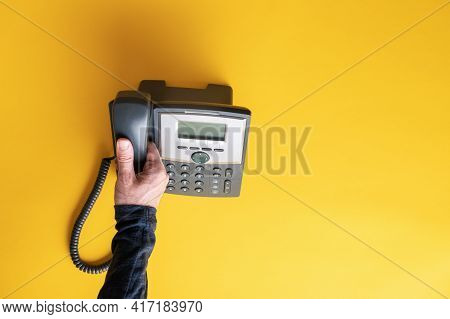 Top View Of Male Hand Picking Up Telephone Receiver Of A Black Landline Phone. Over Yellow Backgroun