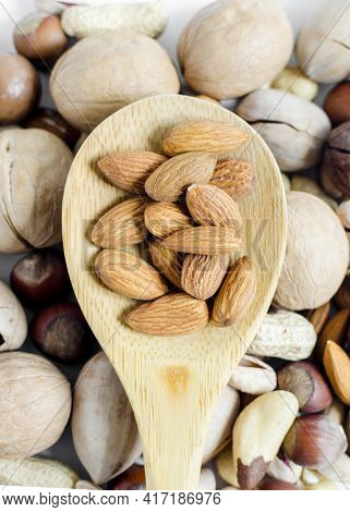 Nuts Almonds In A Wooden Spoon On The Background Of A Scattering Of Different Nuts Assorted Nuts Ver