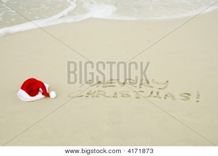 Santa Hat And Merry Christmas Text On A Beach