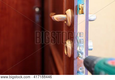 Screwing A Screw Into The Lock On The Front Door Using A Screw Gun