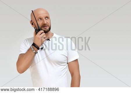 A Security Guard With A Walkie-talkie, A Bald 40-year-old Man Talking On A Walkie-talkie, Isolate