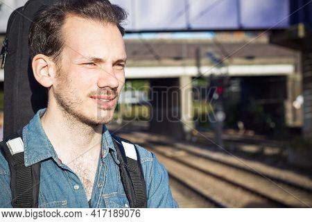 Portrait Of A Squinting Young Man Waiting For Train On Platform, Running Out Of Patience