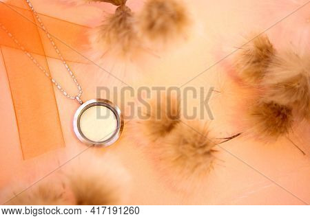 Silver Necklace Shining On Orange Background With White Flowers. Luxury Silver Jewelry Chains With G