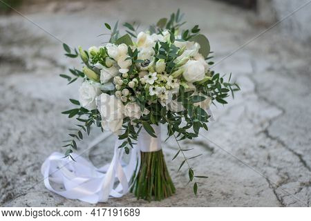 Beautiful Bridal Bouquet Of White Flowers And Greenery, Decorated With Long Silk Ribbon Lies On A Gr