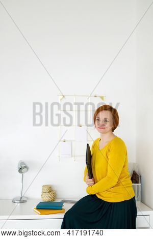 Red Haired Woman In A Yellow Sweater Sits On A White Table Against The Background Of A White Wall, H