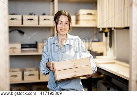 Portrait Of A Young Handywoman Holding Wooden Toolbox In The Workshop. Concept Of Organization In Ho