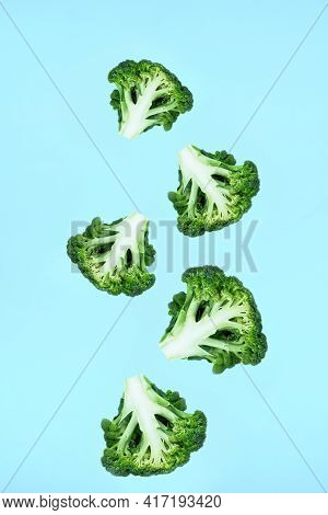 Falling Soaring Green Broccoli Slices On A Blue Background. Concept Of Flying Food, Green Vegetables