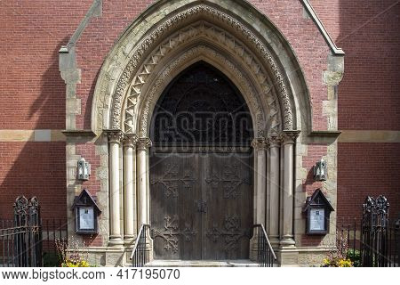 Boston, Ma - April 8 2021: Victorian Gothic Building With Red Brick Facade. Arched Door Into The Chu
