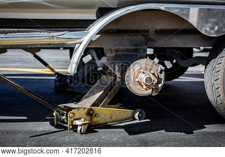 Close up view of a car jack lifting up a boat trailer that needs a new tire. Need new tires?