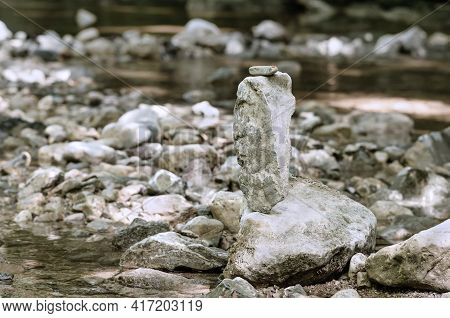 Stacked Rocks, Balancing In A Streambed. Balanced Rock Pile At A Creek, With A Small Red Ladybug On