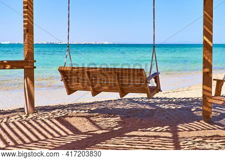 Beautiful Cozy Landscape With The Sea And Swings. Swing Hanging From A Branch Of A Tree On The Beach
