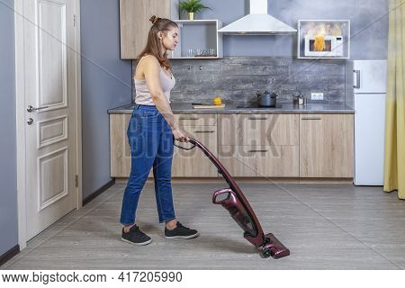 Microwave Oven Burned Out As Result Of Misuse, Young Woman Vacuums Floor And Does Not Notice That Ho