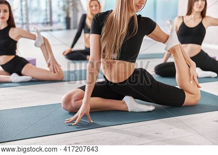 Group Of Female Athletes Are Stretching On The Yoga Mat. Intense Fitness Training Workout In Loft In