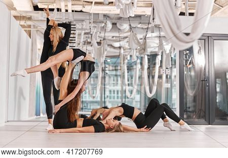 Female Athletes Are Stretching. Intense Fitness Training Workout In Loft Industrial Gym