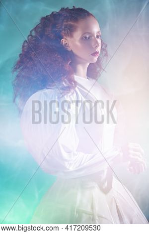 Portrait of a refined fashion model girl with lush red curly hair posing in a long white haute couture dress among flashes and haze on green background. Studio shot. Art and fashion.